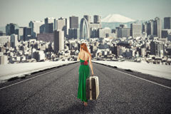Woman with suitcase walking on road towards city talking on phone. Portrait beautiful young woman with suitcase baggage walking on road talking on mobile phone Stock Images