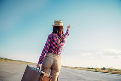 Woman with suitcase waves her hand away Stock Photo