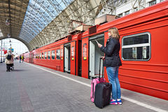Woman with suitcases near train waiting for departure on station Royalty Free Stock Photo