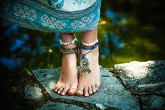 Woman barefoot boho summer fashion style jewelry. Woman summer boho fashion style barefoot with jewelry anklets and rings stand on stone outdoor summer day stock photos