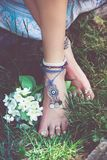 Woman summer boho fashion style details on barefoot anklets and. Rings outdoor  in grass Royalty Free Stock Photos