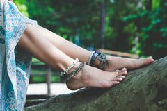 Woman summer boho fashion style details on barefoot anklets and. Rings outdoor  lean on tree Royalty Free Stock Photos