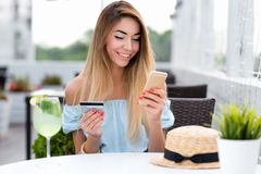 Woman summer cafe, hand credit card phone, pays purchase, orders goods, writes off money account. Contactless payment. Breakfast lunch. Online app enters royalty free stock photography
