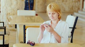 A woman in summer clothes is resting in a cafe, using a telephone. On vacation in connection with the concept.  stock video