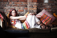 Woman in summer clothes resting on sofa Royalty Free Stock Photo