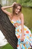 Woman in summer colorful dress laying on tree. Posing at camera in park Stock Photos