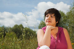 Woman in summer day thinks of what that on nature Royalty Free Stock Photo