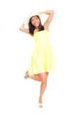 Woman in summer dress. Playful and cheerful. Isolated on white background in full length. Beautiful fresh young mixed race ethnic female model in yellow dress Royalty Free Stock Images