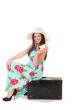 Woman in summer dress with hat and money sitting on a black case Stock Images