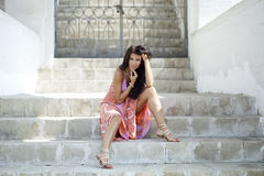 Woman in summer dress sitting on the stone steps Royalty Free Stock Images