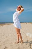 Woman in summer dress standing on sand Stock Photos