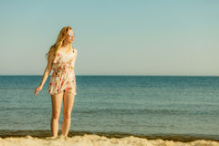 Woman in summer dress walking on beach Royalty Free Stock Image