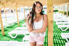 Woman summer fashion. Sexy beautiful female Model With Fit Body, Sunglasses in Dress Posing At Luxury pool Resort. Stock Photo