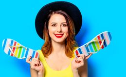Woman with summer flip-flops. Portrait of young smiling red-haired white european woman in hat with summer flip-flops on blue background royalty free stock image