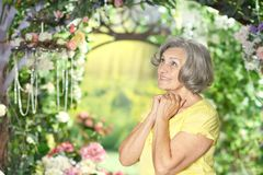 Woman in summer garden. Portrait of beautiful amazed elderly woman in summer garden Stock Images