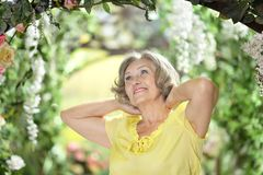 Woman in summer garden. Portrait of beautiful amazed elderly woman in summer garden Stock Photo