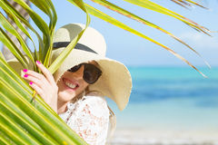Woman with summer hat on the beach hiding behind palm leaf Royalty Free Stock Photo