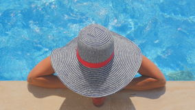 Woman in summer hat drinking cocktail by the pool, top view stock video