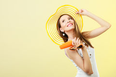 Woman in summer hat holds sunglasses sunscreen lotion Stock Photos