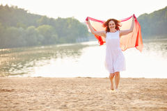 Woman in summer at lake. Woman walking in summer at lake beach with waving scarf Royalty Free Stock Photo