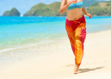 Woman in summer loose trousers running on tropical beach Stock Photos