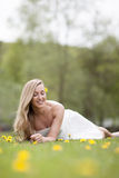 Woman in summer meadow. Attractive young woman with blond hair relaxing in flowery field or meadow Royalty Free Stock Image