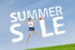 Woman with summer sale sign. Excited woman jumping on the meadow with cloud design of summer sale sign Stock Images