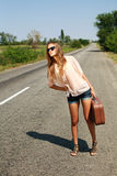 Woman in summer with suitcase hitchhiking on road in countryside. Young woman in the summer with a suitcase hitchhiking on the road in the countryside Stock Photography
