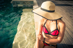 Woman in summer vacation sitting at swimming pool Royalty Free Stock Image