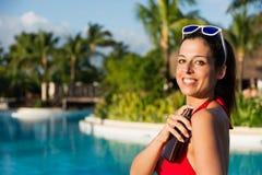 Woman on summer vacation using suntan lotion bottle Royalty Free Stock Photos
