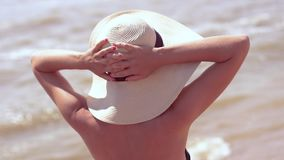Woman in summer vacation wearing straw hat enjoying the view at the ocean. Woman in summer vacation wearing straw hat and beach dress enjoying the view at the stock video footage