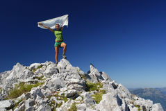 Woman on summit. Hiker woman at mountain top summit holding a white scarf Stock Image