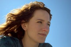 Woman in the sun. Portrait of a young woman with brown hair, sitting on a beach in a sunny windy day, with the sun behind her head Stock Image