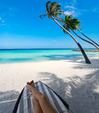 Woman on sun bed under palm tree at tropical island. Woman on sunbed under palm tree at tropical island Royalty Free Stock Photo
