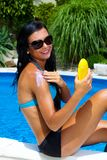 Woman with sun cream by the pool