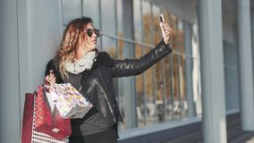 Woman Holding a Bunch of Shopping Bags Doing Selfie on the Street. Woman in sun glasses a black leather jacket, black jeans Holding a Bunch of Shopping Bags stock footage