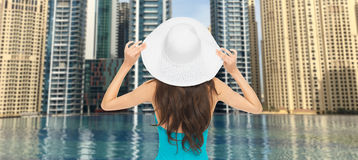 Woman in sun hat from back over dubai city pool stock images
