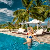 Woman with hat at beach pool in Maldives. Woman with sun hat at beach pool in Maldives Stock Photos