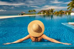 Woman with hat at beach pool in Maldives. Woman with sun hat at beach pool in Maldives Stock Photo