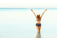 Woman in sun hat and bikini enjoying looking view of beach on su Royalty Free Stock Photos