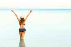 Woman in sun hat and bikini enjoying looking view of beach on su Royalty Free Stock Photography
