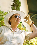 Woman in Sun Hat and Gardening Gloves Royalty Free Stock Photography