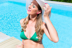 Woman with sun hat relaxing at swimming pool Royalty Free Stock Image