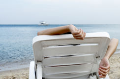 Woman on sun lounger on sea shore Royalty Free Stock Photo