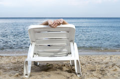 Woman on sun lounger on sea shore Stock Photography