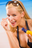 Woman with sun-protection cream. Young woman with sun-protection cream on beach. Focus on woman