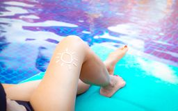 Woman with sun shape of sunscreen cream apply on tan legs. Woman sit at poolside. Woman relax on chair beside swimming pool royalty free stock images