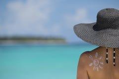 Woman with sun-shaped sun cream on beach Stock Photo
