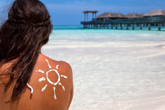 Woman with sun-shaped sun lotion drawing on her back. Sitting on a beach at the Maldives Royalty Free Stock Photo