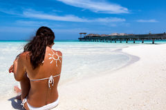 Woman with sun-shaped sunscreen drawing on her back. Sitting on the Beach at the Maldives Royalty Free Stock Photos